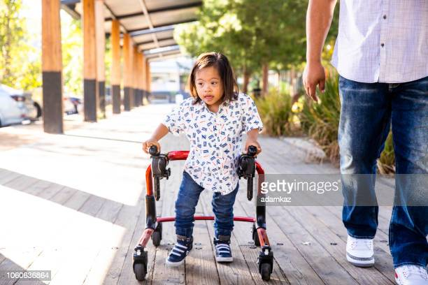 Hispanic Boy with Down's Syndrome Using Walker with Dad