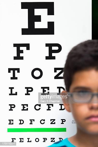Hispanic boy with glasses and eye chart