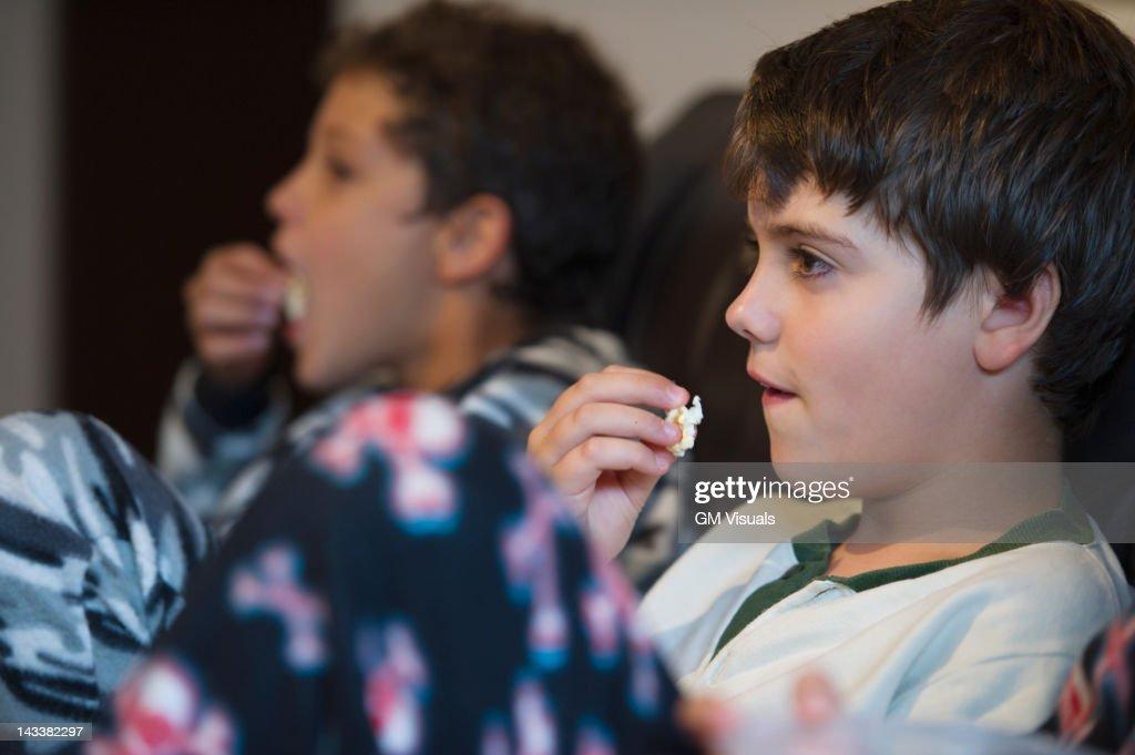 Hispanic boys eating popcorn and watching television : Stock Photo