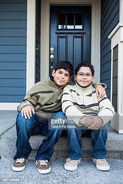 Hispanic boys hugging on front stoop