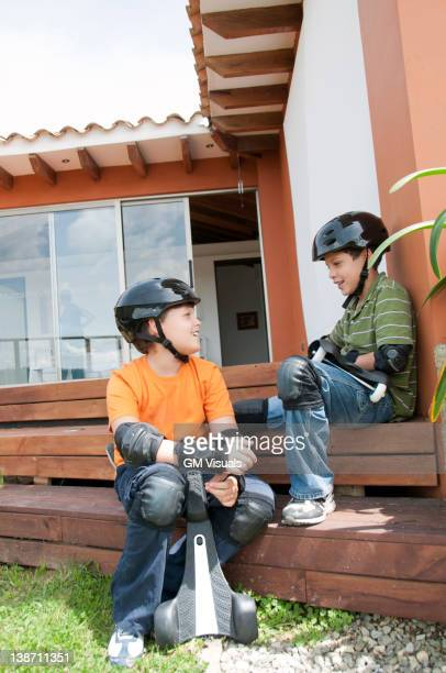 hispanic boys in pads and helmets holding skateboards - padding stock pictures, royalty-free photos & images