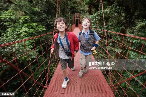 Hispanic boys on suspension bridge in woods