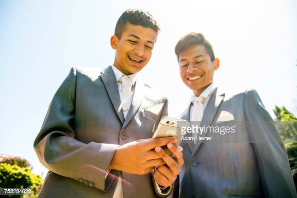 hispanic boys wearing suits texting on cell phone - 14 15 anni foto e immagini stock