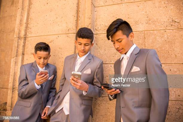 hispanic boys wearing suits texting on cell phones - 14 15 anni foto e immagini stock