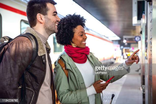 hispanic brazilian couple in italy - traveling county by train - vending machine stock photos and pictures