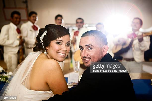 Hispanic bride and groom at wedding reception