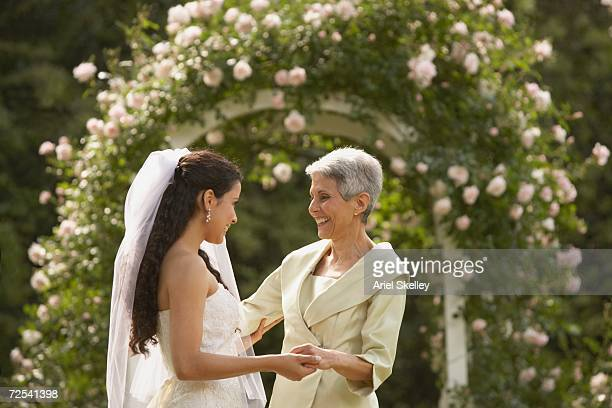 Hispanic bride and mother smiling at each other