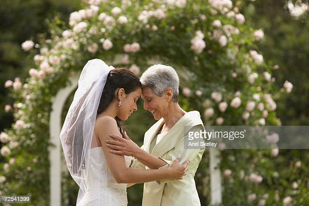 Hispanic bride and mother touching foreheads