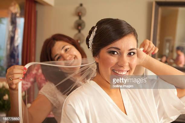 Hispanic bride arranging veil