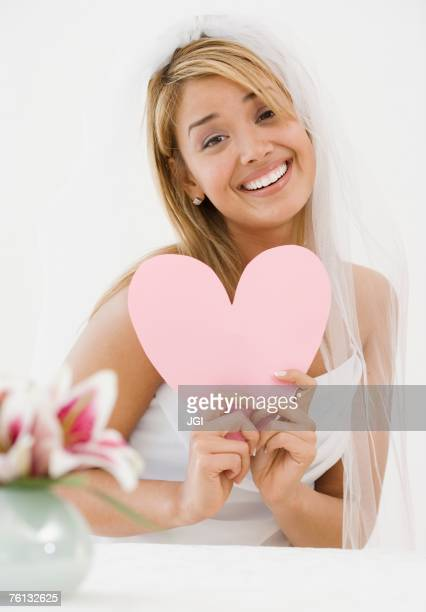 hispanic bride holding paper cutout heart - veil stock photos and pictures