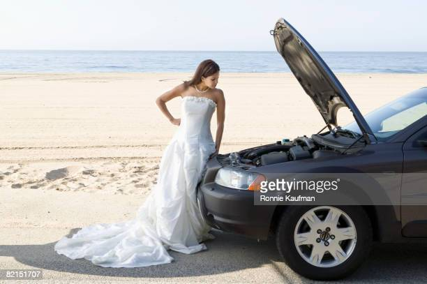 hispanic bride next to car with hood up - zuma beach stock photos and pictures