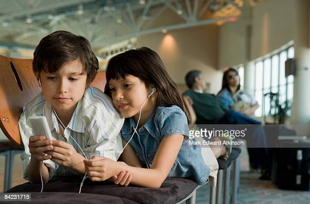 Hispanic brother and sister listening to mp3 player in airport