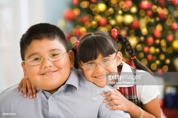 hispanic brother and sister smiling near christmas tree - chubby boy stock pictures, royalty-free photos & images