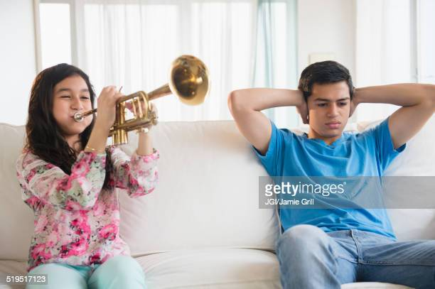 Hispanic brother covering his ears as sister practices trumpet in living room