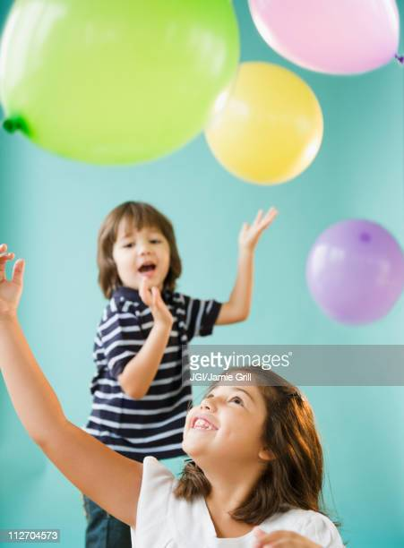 Hispanic brothers and sisters playing with balloons