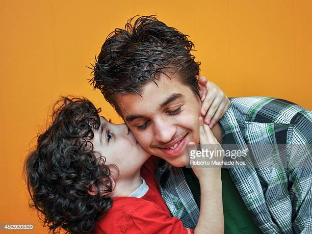 Hispanic brothers showing their familial affection by hugging and kissing
