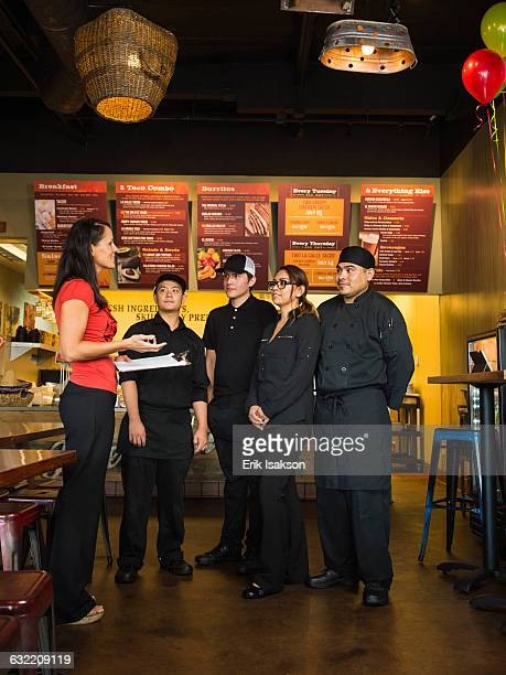 Hispanic business owner and employees talking in cafe
