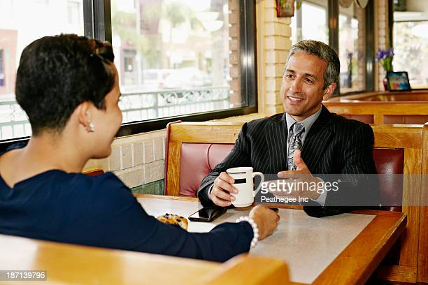 Hispanic business people talking in restaurant