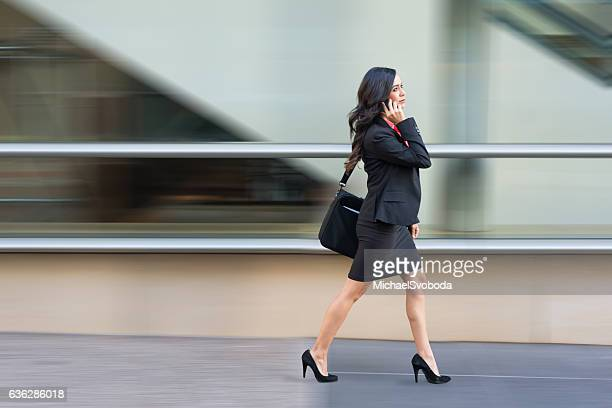 hispanic business women on phone walking in a rush - white skirt stock pictures, royalty-free photos & images