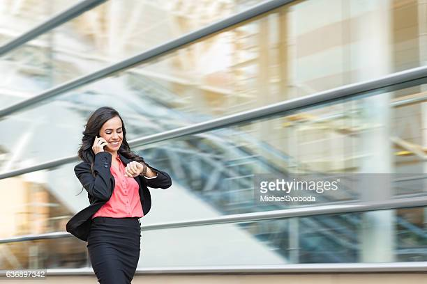 hispanic business women on phone walking in a rush - día fotografías e imágenes de stock