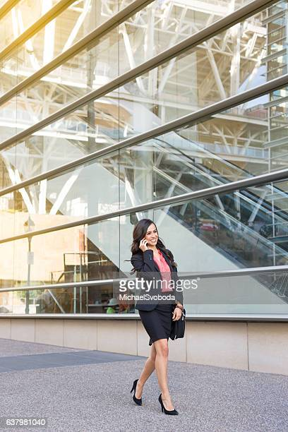 hispanic business women on phone walking in a rush - mexican business women stock photos and pictures