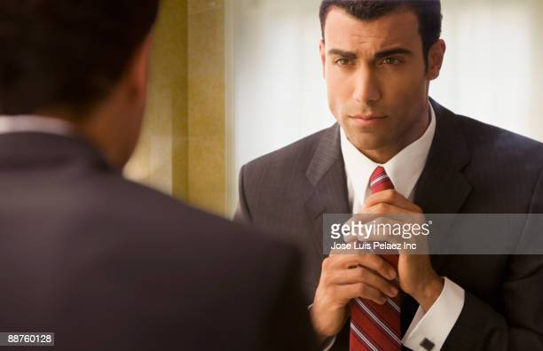 Hispanic businessman adjusting tie