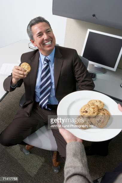 Hispanic businessman being given cookies