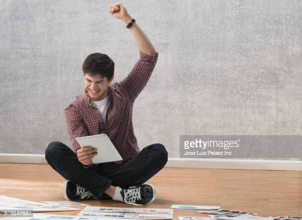 hispanic businessman cheering at digital tablet on office floor - 胡坐 ストックフォトと画像
