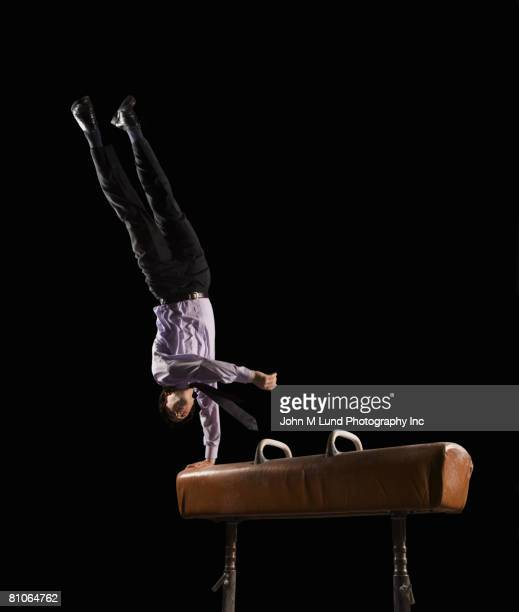 hispanic businessman dismounting from pommel horse - john lund stock pictures, royalty-free photos & images