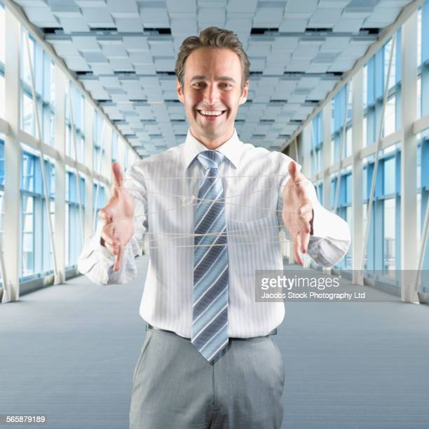 Hispanic businessman displaying cats cradle in office