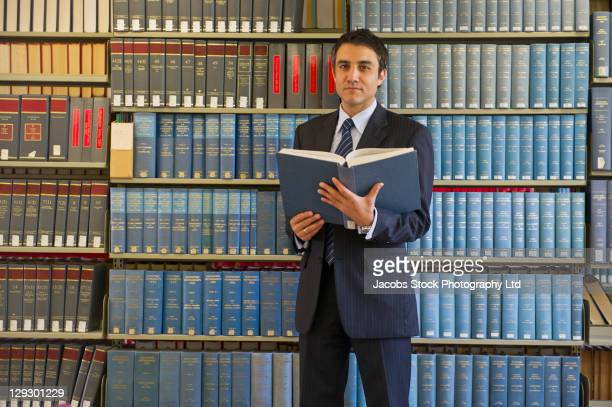 hispanic businessman doing research in library - man holding book stock pictures, royalty-free photos & images
