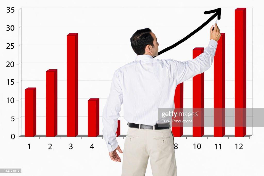 Hispanic businessman drawing bar graph on board : Stock Photo
