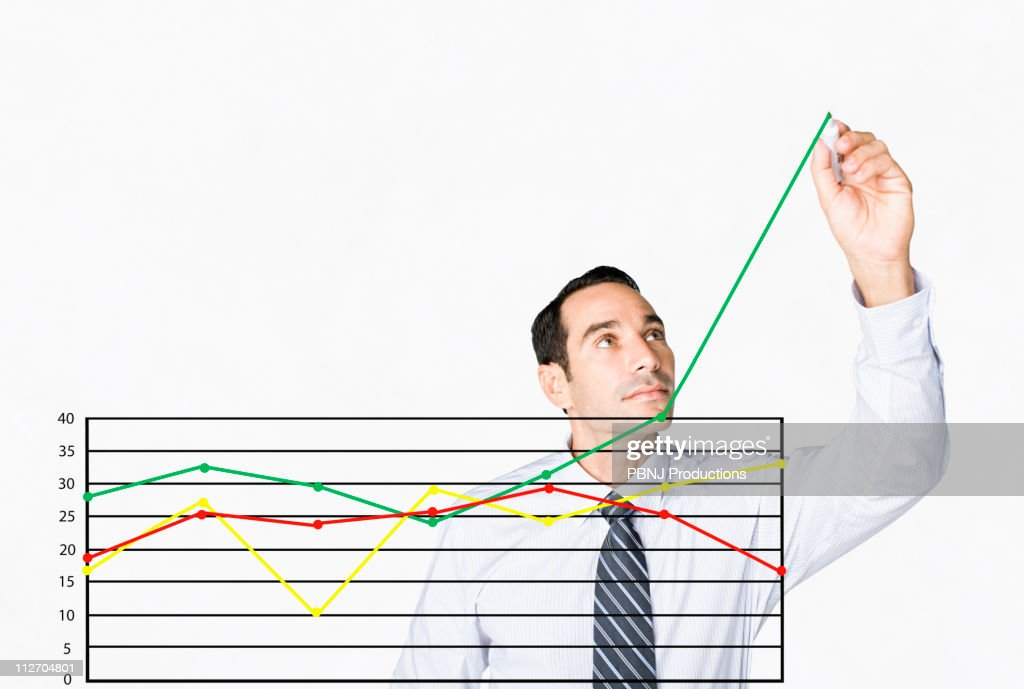 Hispanic businessman drawing chart on clear board : Stock Photo