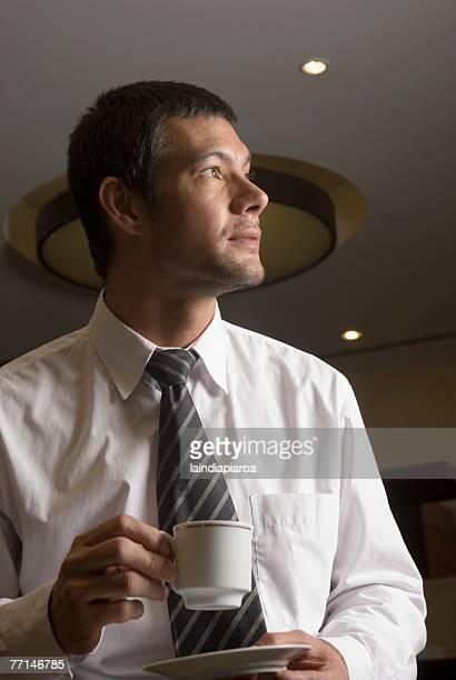 Hispanic businessman drinking coffee