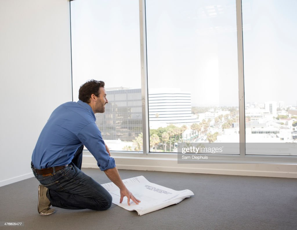 Hispanic businessman examining blueprints in office : Stock Photo