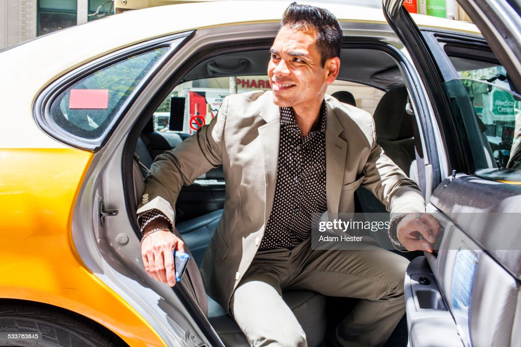 Hispanic businessman exiting taxi : Foto stock