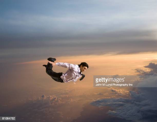 Hispanic businessman flying in air