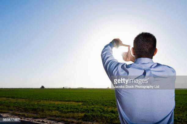 Hispanic businessman framing sunshine over rural field