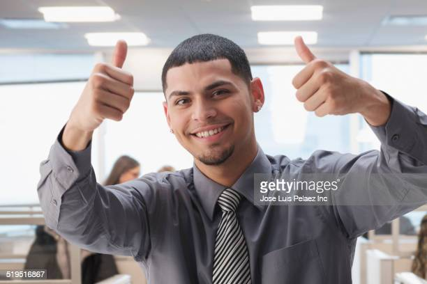 Hispanic businessman gesturing thumbs up in office