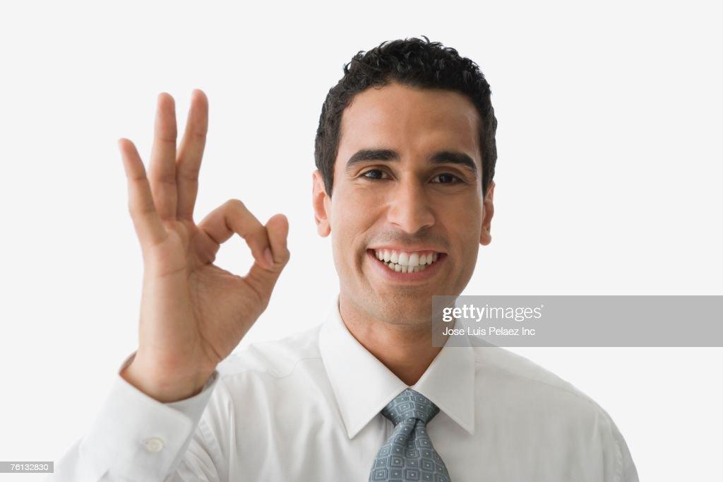 Hispanic businessman giving okay hand gesture : ストックフォト