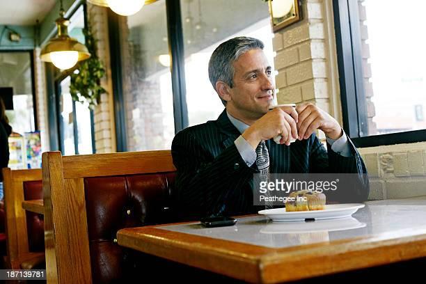 Hispanic businessman having coffee in restaurant