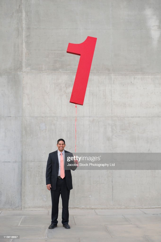 Hispanic businessman holding balloon shaped like number 1 : Foto de stock