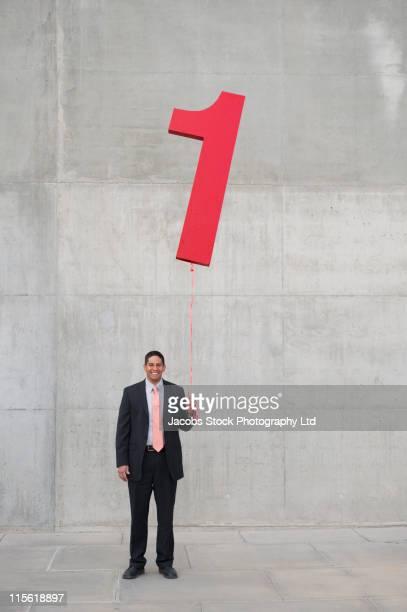 Hispanic businessman holding balloon shaped like number 1