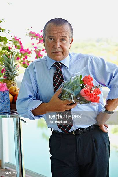 hispanic businessman holding bouquet of flowers - impatience flowers stock pictures, royalty-free photos & images