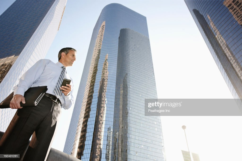 Hispanic businessman holding cell phone and notebook outdoors : Stock Photo