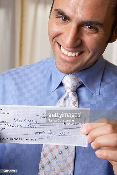 hispanic businessman holding check - millionnaire stock photos and pictures