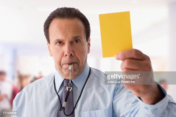 Hispanic businessman holding yellow card and blowing whistle