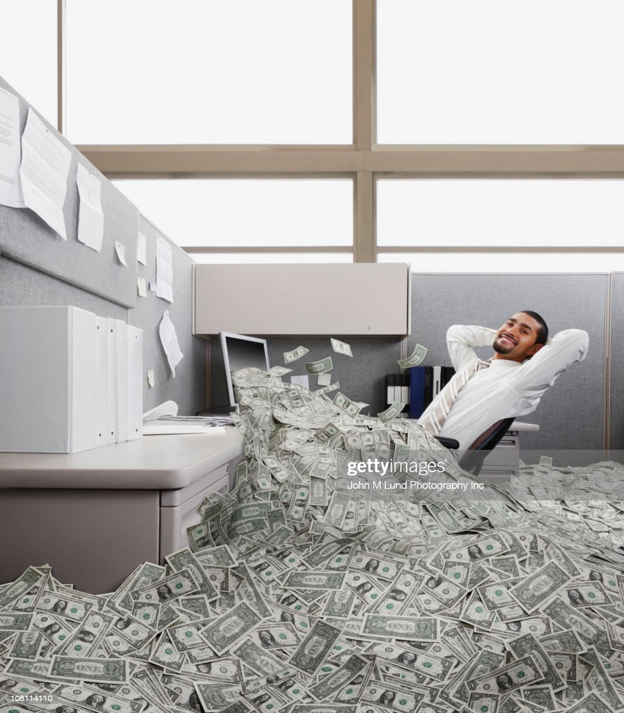Hispanic businessman in cubicle covered in one dollar bills : Stock Photo