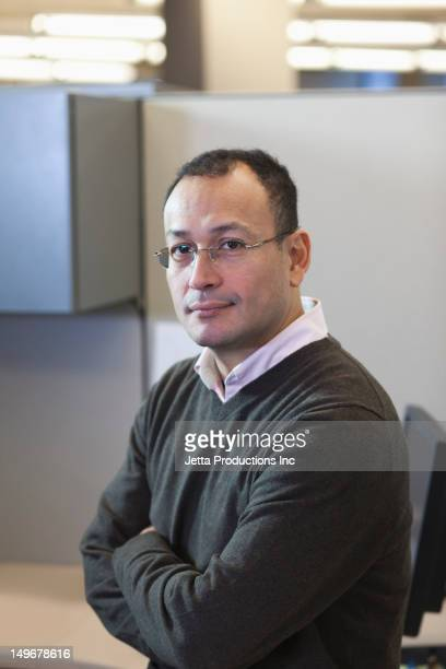 Hispanic businessman in office with arms crossed