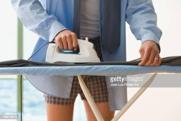Hispanic businessman ironing pants